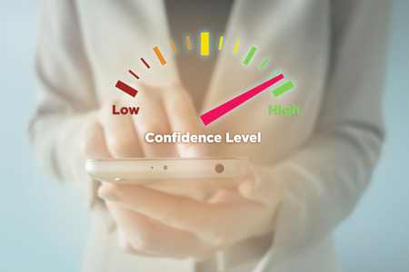 self assurance: Close-up Of young businesswoman using smartphone with High Confidence Level meter