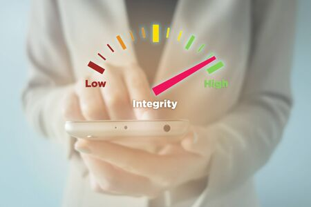 Close-up Of young businesswoman using smartphone with High Integrity meter Stock Photo