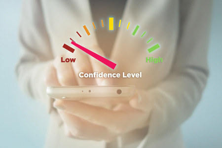 self assurance: Close-up Of young businesswoman using smartphone with Low Confidence Level meter