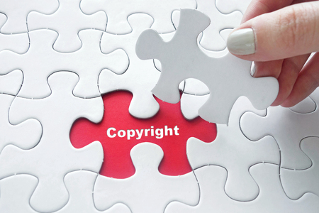dispensation: Close up of girls hand placing the last jigsaw puzzle piece with word Copyright Stock Photo