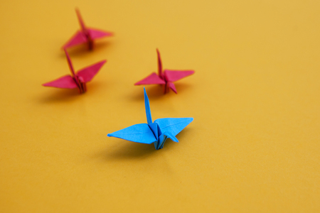 Leadership Concept - One odd paper crane in a group as a leader