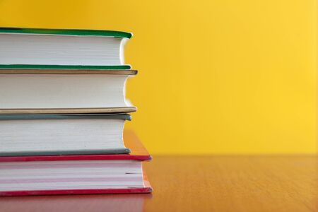 Copyspace of stack books over yellow background Reklamní fotografie