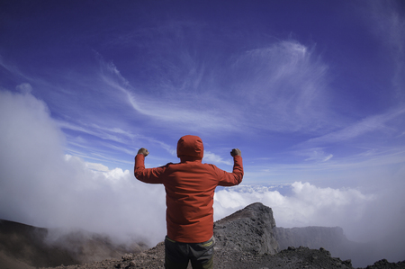 Victory concept: A man raising his hand at the peak of Mount Kerinchi Reklamní fotografie
