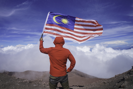 A man holding national flag of Malaysia near mountain cliff