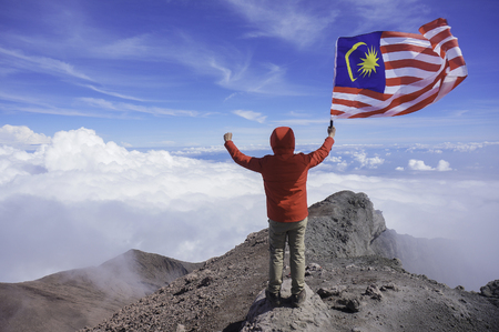 Copyspace: A man holding national flag of Malaysia near mountain cliff Reklamní fotografie