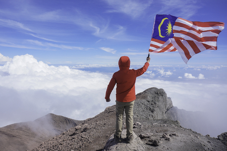 A man holding a Malaysian flag at the peak of Mount Kerinchi