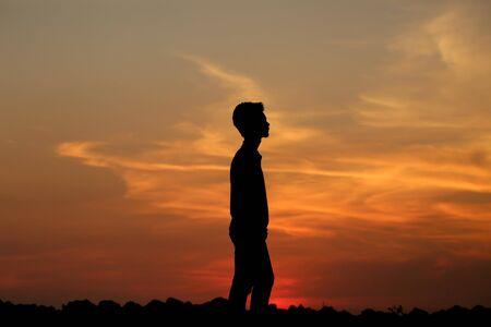eine Silhouette eines Jungen bei Sonnenuntergang