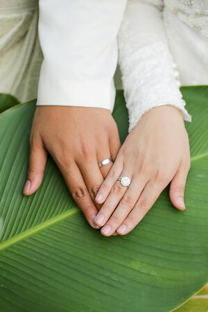 newly weds putting their hands together on a green leaf. the couple wear a beautiful and luxury wedding ring