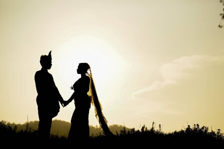 silhouette of a malay newly weds couple on a traditional outfit during sunset