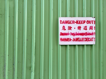 out of danger: A shot of danger keep out sign with translation in several other languages on a green stripe background.