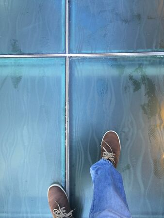 jeans: A top view shot of a person walking on glass floor.
