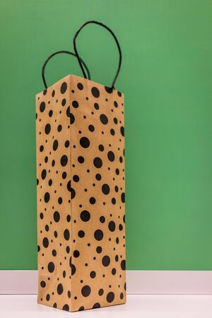 paperbag: A shot of dotted paperbag shot against green background. Stock Photo