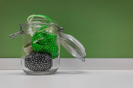 green background: A shot of colorful ribbons in a glass container shot against a green background.