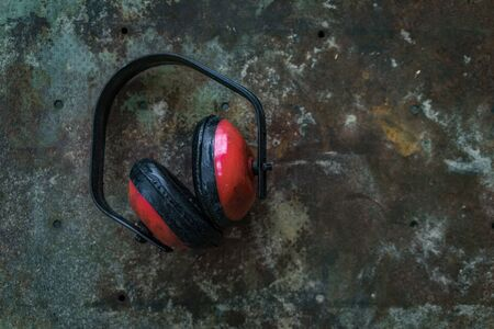 noise isolation: A shot of an ear protection gear on a rustic surface.