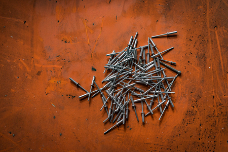 shafts: A shot of rivets or mechanical fasteners over an orange background. Stock Photo