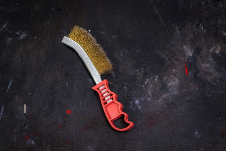 workbench: A shot of a wire brush on a dirty workbench.