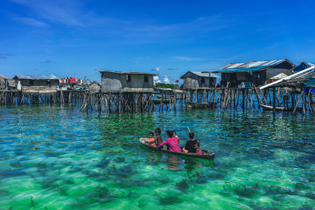 sabah: Omadal Island, Sabah Malaysia - April 30, 2016 : A shot of a family getting around the fishermen village in a wooden boat. The shot was taken at Omadal Island, Sabah Malaysia. Editorial