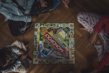 pahang: Frasers Hill, Pahang Malaysia - August 13, 2016 : A top view shot of a family playing board game together.