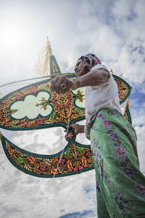 Kampung Mek Mas, Kota Bahru, Kelantan  Malaysia - July 15, 2017 : A low angle shot of an elder waiting for the right moment to fly his uniquely design kite.
