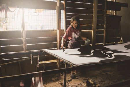 Kota Bahru, Kelantan Malaysia, 15th July, 2017 - A shot of a local Kelantanese woman coloring the batik outlined by wax. The shot was taken at one of the villages in Kelantan that practices the traditional ways of producing batik fabrics.