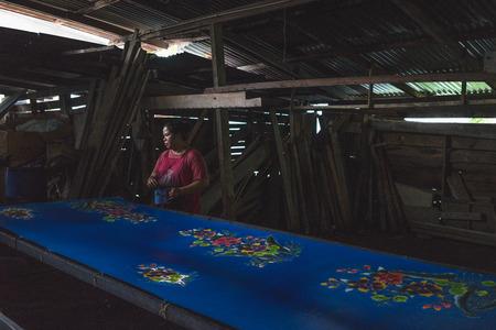Kota Bahru, Kelantan Malaysia, 15th July, 2017 - Local Kelantanese woman coloring the batik outlined by wax. The shot was taken at one of the villages in Kelantan that practices the traditional ways of producing batik.
