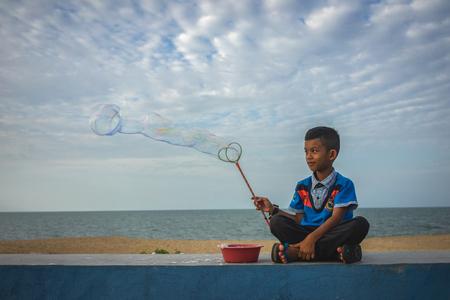 Kota Bahru, Kelantan : 21st July 2018 - Shot of a boy making bubbles by the ocean.