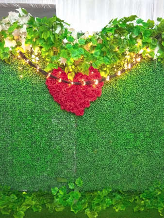 a background wall decorated with green grass and a red heart in the middle, and orange decorative lights.