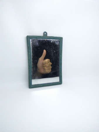 hand raised thumbs up reflected in mirror isolated on white background