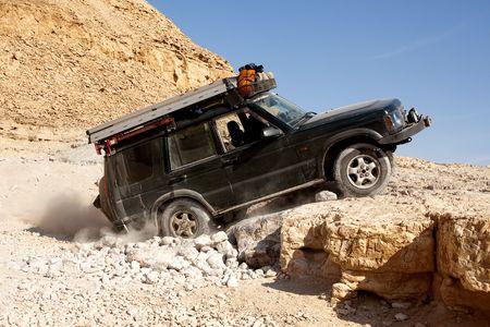 Landrover climbing up a rock in the desert photo