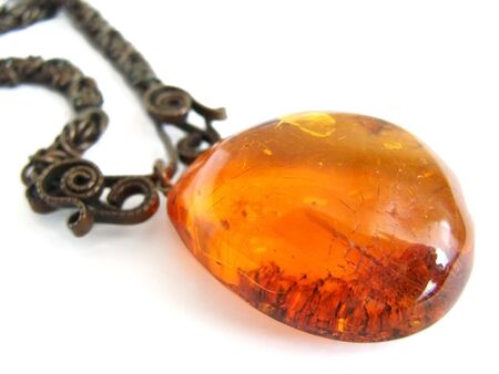 Old vintage amber pendant on white photo