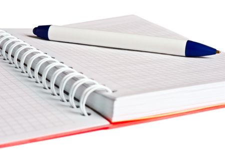 closeup of spiral notebook with orange cover and white-and-blue pen, isolated on white photo