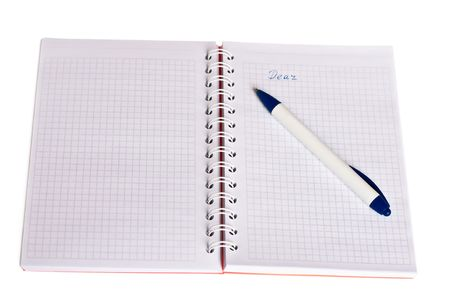 spiral notebook with orange cover, white-and-blue pen and handwriting word dear photo