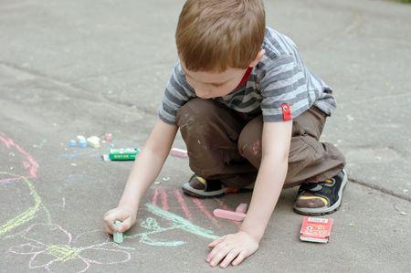 アスファルトの上チョークで描く少年 写真素材