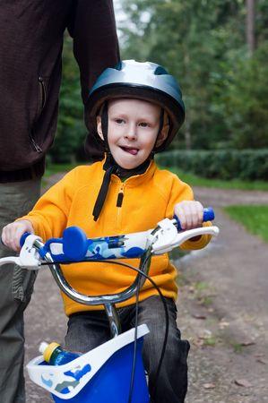 父は自転車に乗ることを学ぶ彼の息子を助けます。