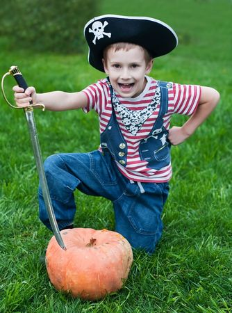 small sword: boy wearing pirate costume attacks pumpkin with sword Stock Photo