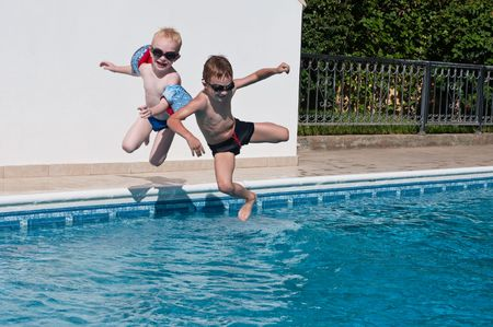 two happy brothers jumping into swimming pool photo