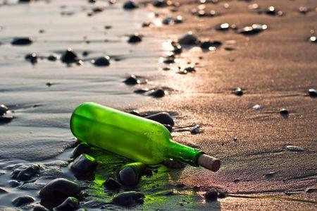 夕暮れ時のビーチでの緑色のボトル
