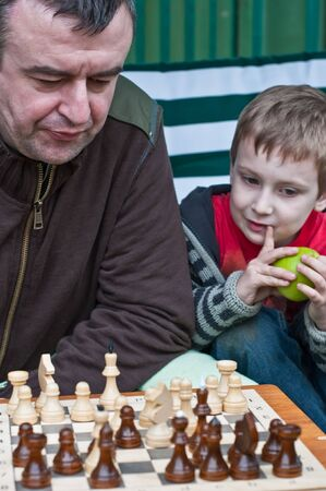 father and son playing chess outdoors photo