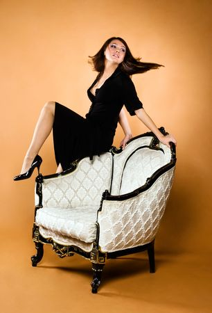 young beautiful woman and antique armchair photo
