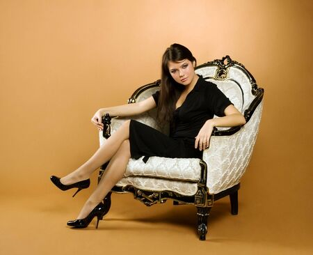 young beautiful woman sitting in antique armchair photo