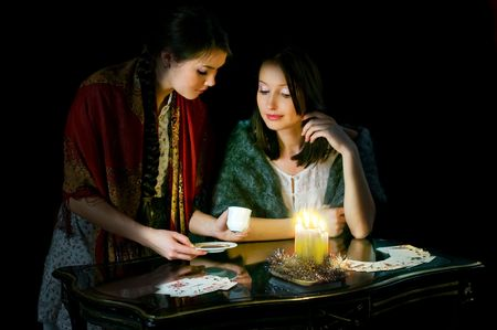 Christmastide fortune-telling: two girls reading coffee grounds photo