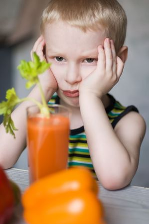 young sad boy doesnt like vegetables photo
