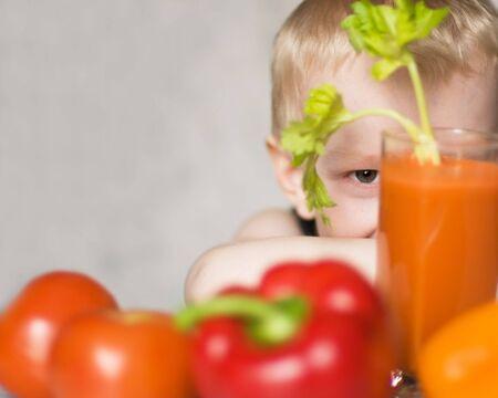 野菜の間に隠れて笑って少年 写真素材