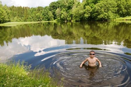 夏の暑い日に池で泳いでいる少年
