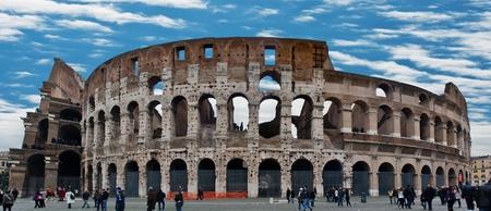 amphitheatre: Roman Coliseum (Flavian Amphitheatre). Tourists milling around Coliseum, the walkways and terraces.