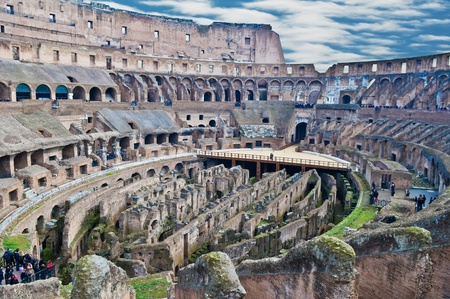 Internal wide angle view of Roman Colosseum (Flavian Amphitheatre) showing passages under the arena, the corridors, the stands and the outer walls. Tourists milling around the walkways and terraces.