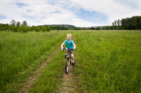 nice boy cycling in the field, country, non-urban, Russia photo
