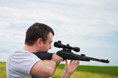 sniper training: man aiming, looking into the scope of his rifle
