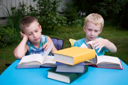 8-year and 6-year boys reading books outdoors Imagens