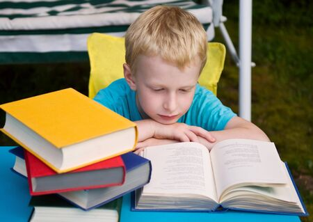 6-year boy reading book outdoors photo